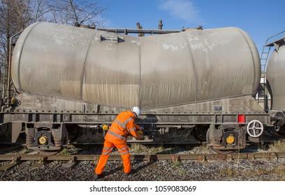 A railway worker in hi viz clothing repairing a tanker wagon at the rail side.