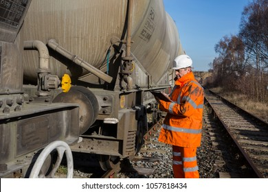 A railway worker in high visibility clothing inspecting a railroad wagon during a scheduled maintenance inspection.