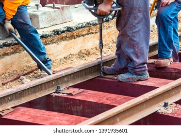 Railway workers bolting track rail. Detail worker with Light portable sleepers drilling machine