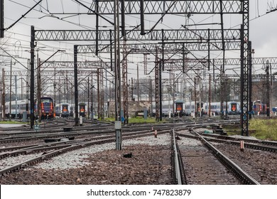 Railway yard with trains on tracks under the cloudy sky