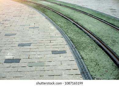 railways on the green street in the daylight