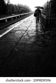 Rain bad weather. Man with an umbrella on a railway platform