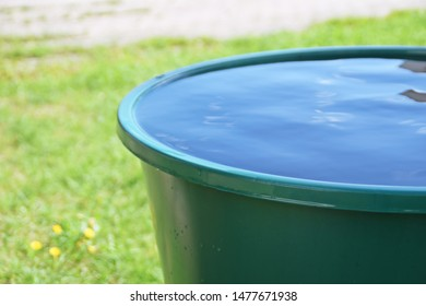 A rain barrel filled with water stands on a green meadow in the summer after a summer storm