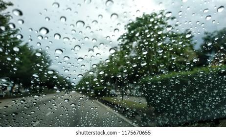 rain behind a window. rain drops on glass. cars on the road. heavy rain