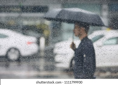 Rain in city. Young man holding umbrella walking in the street. Selective focus on  raindrops on the window.