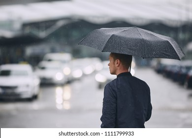 Rain in city. Young man holding umbrella walking in the street.