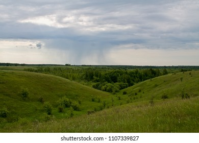 a rain cloud in the field, in the distance it rains, green hills, a beautiful green panorama of the field with rain