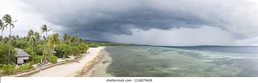 Rain clouds drift over a luxurious, tropical island resort in Wakatobi National Park, Indonesia. This area harbors an amazing array of marine biodiversity and is within the Coral Triangle.