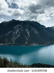 Rain clouds gather above the mountain top next to the lake in a summer day, flying the drone. Austrian weather is unpredictable.