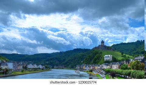 Rain clouds gathering over Cochem castle, perched on the bank of the river Moselle, Germany. The castle has vineyards right in front, winding down to the quaint center of Cochem town
