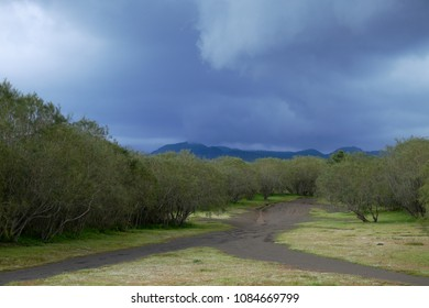 rain clouds on bifurcation of dirt road in Etna Park, Sicily