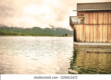 Rain and clouds on the Wolfgangsee in Austria. Morning mist over the Austrian landscape with lake, boat hangars, forests,  pastures, meadows and villages. Vintage style