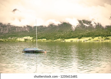 Rain and clouds on the Wolfgangsee in Austria. Morning mist over the Austrian landscape with lake, yacht, forests,  pastures, meadows and villages. Vintage style