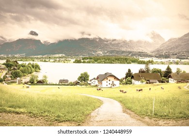 Rain and clouds on the Wolfgangsee in Austria. Morning mist over the Austrian landscape with lake, forests, fields, pastures, meadows and village. Vintage style