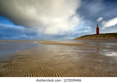 rain clouds over red lighthouse and sea coast, Holland