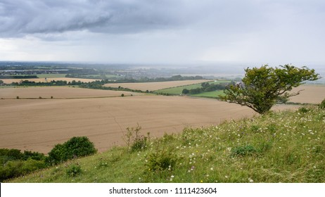 Rain clouds roll over the fields of wheat and pastures in the agricultural plains of Aylesbury Vale, drenching Buckinghamshire villages, viewed from Beacon Hill on the edge of the Chilterns.
