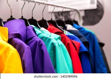 Сolorful rain coats hanging from a shelf