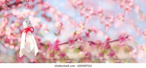 Rain doll, white cloth japanese doll hanged under pink flower tree or Sakura. Teru teru bouzu is the name in japanese of rain doll for anti rain