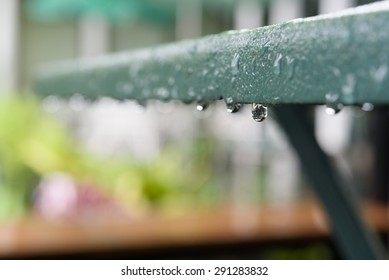 Rain dripping from a green iron table.Feeling lonely