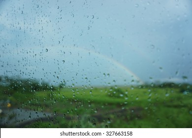 Rain Drop on the car windows with blurry rainbow as background