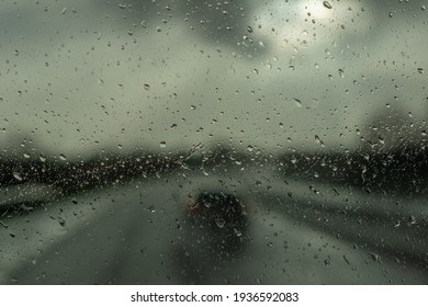 Rain drop on the cars windscreen . Abstract traffic in raining day. Road view through car window with rain .