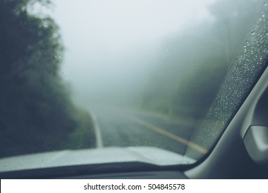 Rain drop on glass of the car with fog or mist in green nature mountain