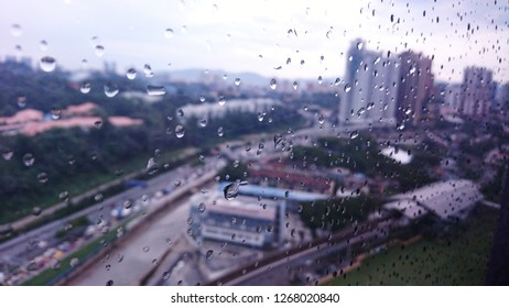 rain drop on window glass with blurred city landscape as background