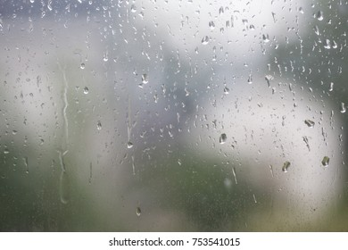 Rain droplets on window glass with a fully blurred background.