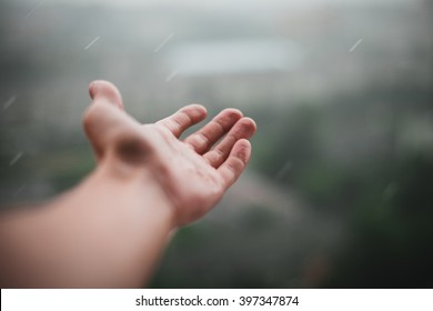Rain is dropping on a man's hand. It is a first rain in this year. Wet smell of rain