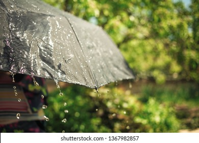 Rain drops falling from a black umbrella concept for bad weather, summer and spring rain