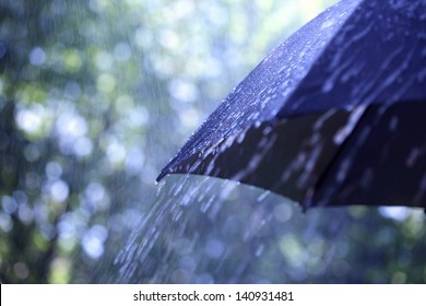 Rain drops falling from a black umbrella