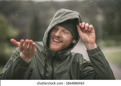 Rain drops. Man in a green coat catching rain drops and smiling