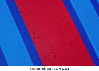 Rain drops on blue and red painted car hood.