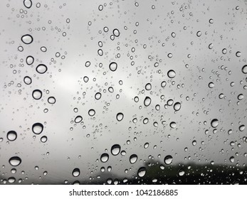 Rain drops on car window glasses surface with cloudy background in city. Natural Pattern.