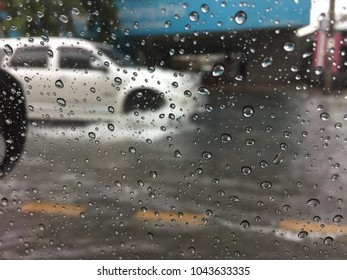 rain drops on car window with cars driving on a flooded road