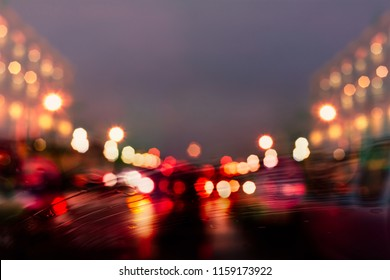Rain drops on the car window with abstract bokeh night city background.