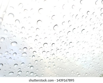 Rain drops on car window glasses surface, water drops natural background.
