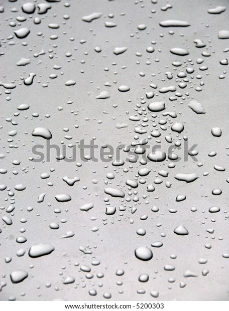 Rain drops on a gray metallic back ground
