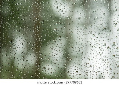 rain drops on home window pane with green forest and grey sky background. Focus on raindrops