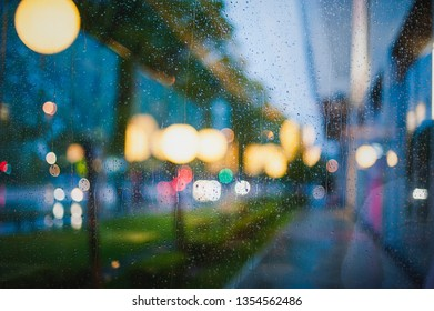 Rain drops on large glass window at the sunset city lights with lots of background bokeh colorful shapes, reflections and shadows. Bright and dark abstract composition with vivid illumination.