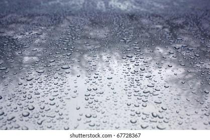 Rain drops on a waxed silver car hood