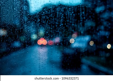 Rain drops on the window. Abstract bokeh of lights on the road. Defocused.