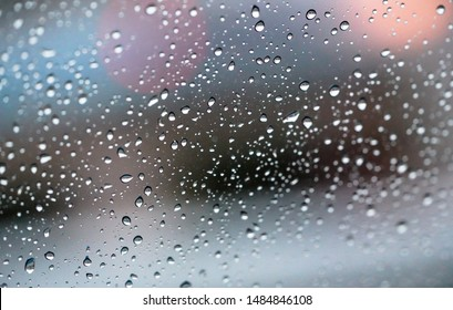 Rain drops on a window with abstract lights with selective focus area. Bokeh background concept.