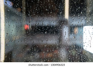Rain drops on the window in the big city. Big building on the background.