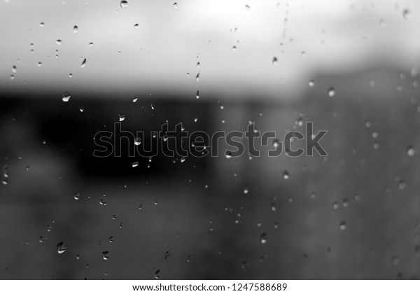 Rain drops on window with blured background in black and white. Seasonal background texture for design.