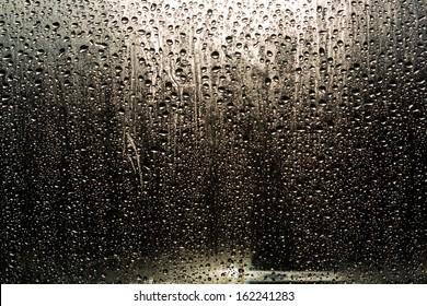 Rain drops on the window on the dark background