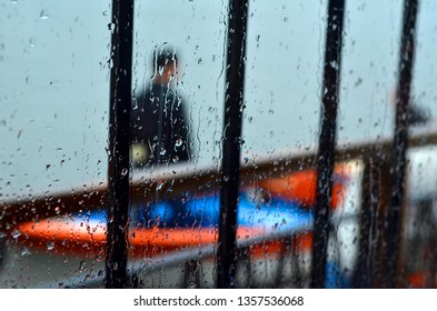 Rain drops on window, fisherman and boat in background