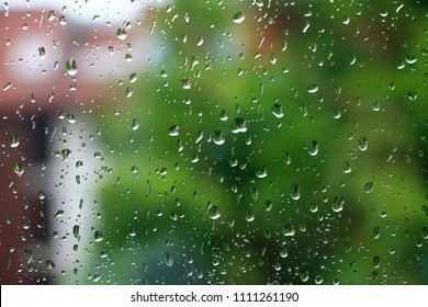 Rain drops on window glass with green in background
