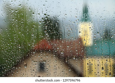 Rain drops on window glass with house and church in background