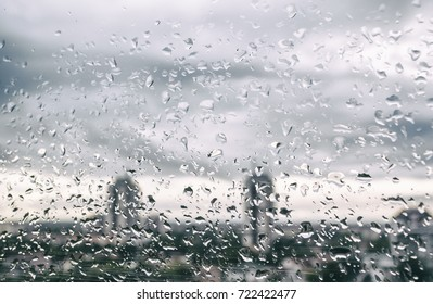 Rain drops on window glass outside texture background water of wonderful heavy rainy day with sky clouds at city